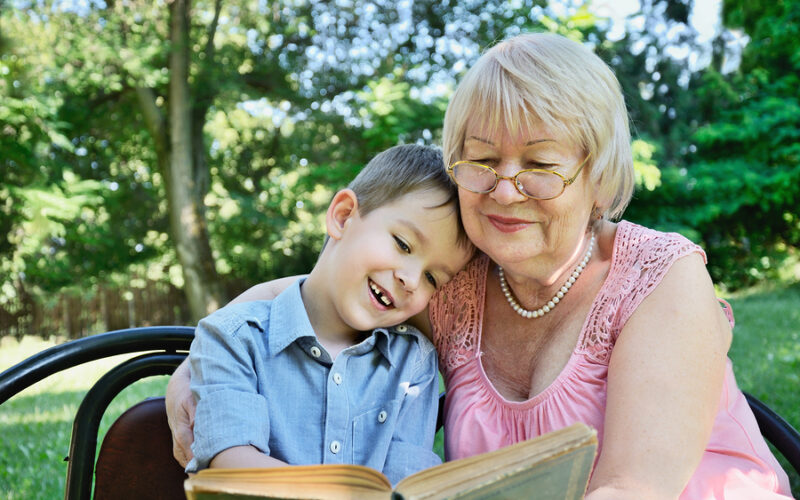 smiling boy and his grandmother sitting in the park and reading a book. horizontal